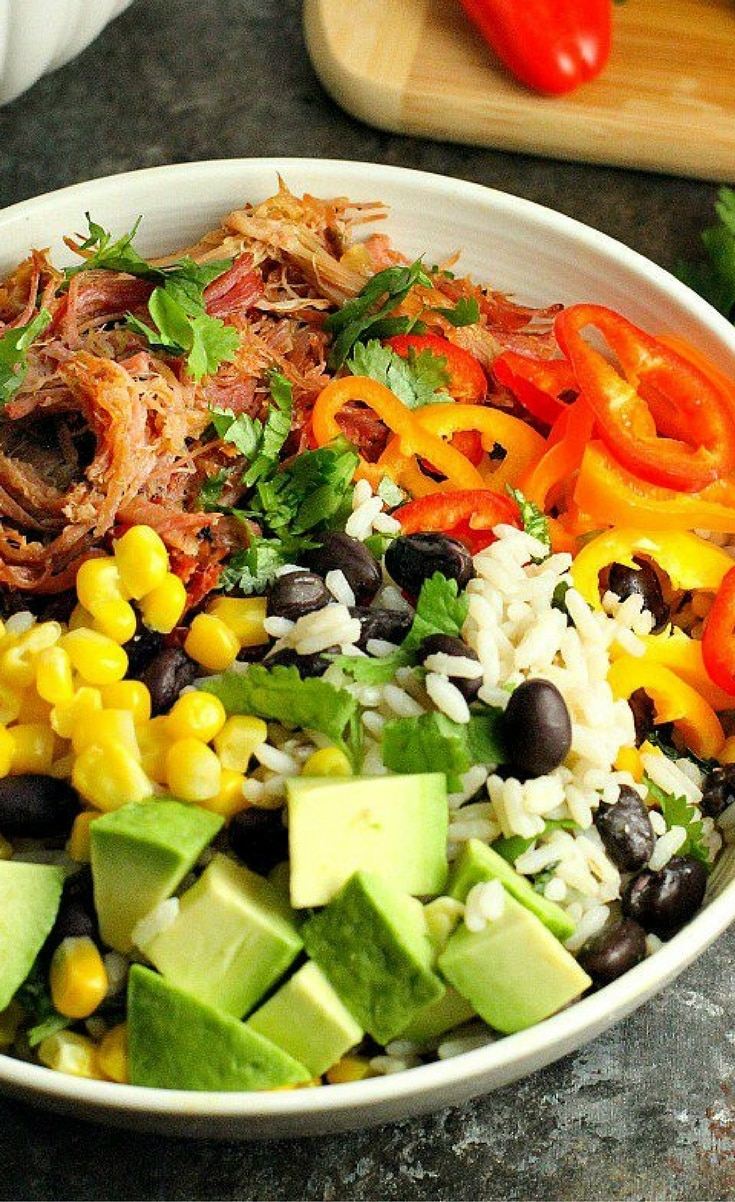 Add a new twist to Mexican night with these Pork Carnitas Burrito Bowls! Black bean cilantro lime rice is topped with flavorful slow cooker pork carnitas and your favorite toppings for a delicious (and healthy) dinner!